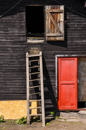 red door: Wooden ladder on a cottage wall with red door