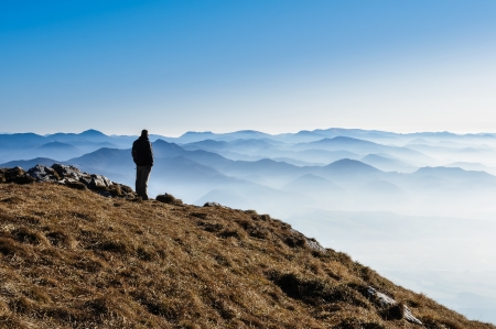 Misty mountain hills and silhouette of a man photo