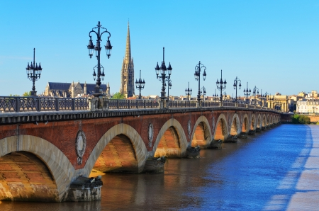 famous industries: Bordeaux river bridge with St Michel cathedral Stock Photo