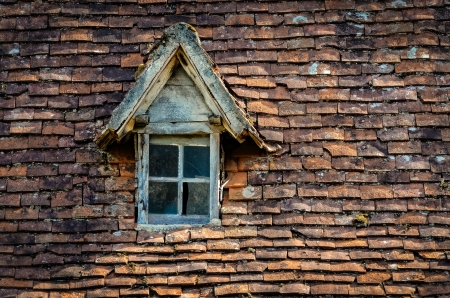 Old orange brick roof with broken glass retro winow photo