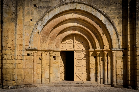 Stone church entrance door and arcs, St Emilion, France photo