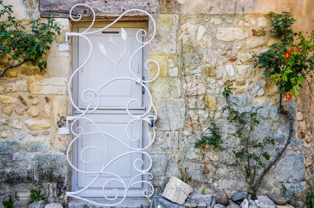 Provence white door in brick wall with metal bars, flowers on the wall photo