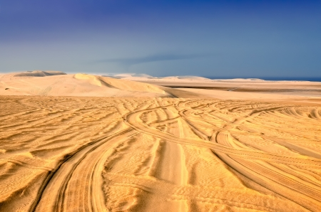 Detail of tyre tracks in sand desert with blue sky background photo