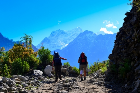 Two people trekking in the mountains with Himalayas in background, Nepal photo