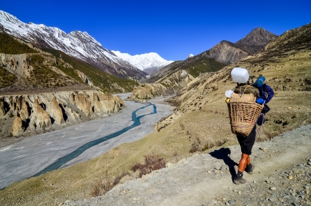 Mountain porter carrying heavy load in Himalayas, Nepal photo