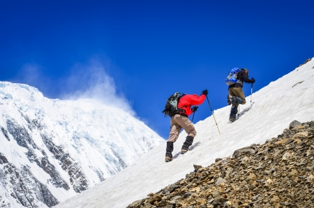 nepal: Two mountain backpackers walking on snow with peaks background, Himalayas Stock Photo