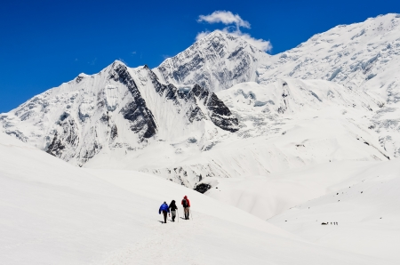 Small group of mountain trekkers in high winter Himalayas mountains, Nepal Stock Photo