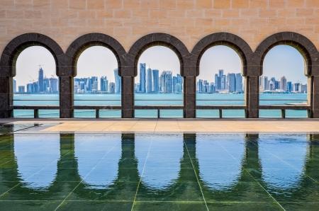Doha skyline gezien door de bogen in het Museum van Islamitische Kunst, Doha, Qatar Stockfoto