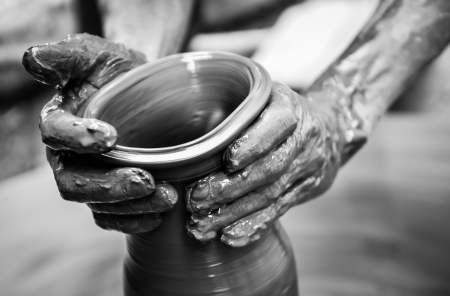Hands of a man creating pottery on wheel, monochrome vintage view