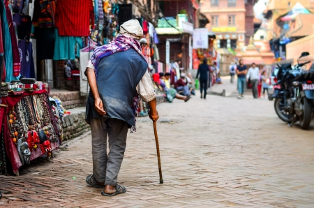 poor health: Poor old man walking with stick in exotic asian street, Nepal Stock Photo