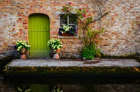 Vintage old wall with greed door and flowers, Bruges, Belgium photo