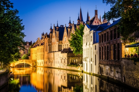 Water canal and medieval houses at night in Bruges, Belgium
