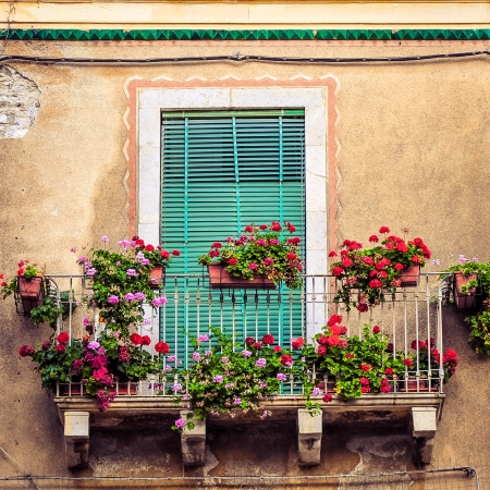 Beautiful vintage balcony with colorful flowers and wooden door 免版税图像