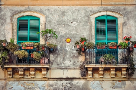 Beautiful vintage balcony with colorful flowers and wooden doors, Mediterranean style 免版税图像