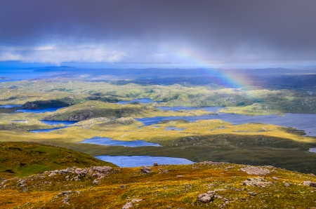 Scenic view of beautiful lakes, clouds and rainbow in Inverpolly area, highlands of Scotland, United Kingdom photo