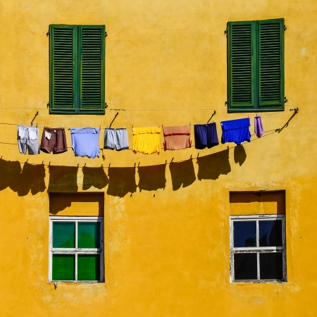 Detail of colorful yellow house walls, windows and drying clothes in square format photo