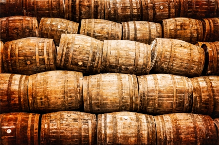 Stacked pile of old whisky and wine wooden barrels in vintage style photo