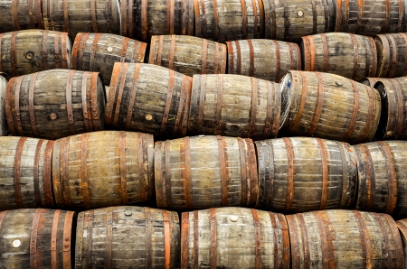 casks: Stacked pile of old whisky and wine wooden barrels and casks