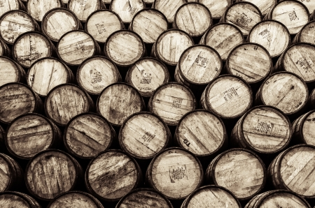 distillery: Detail monochrome view of stacked wine and whisky wooden barrels and casks