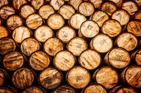 Detail view of stacked whisky and wine wooden barrels in vintage style Stock Photo