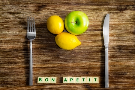 Lemons and apple on wooden vintage table with silverware and Bon apetit sign Banco de Imagens