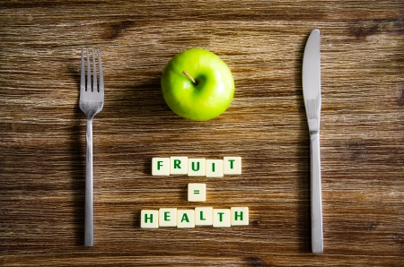 sign equals: Silverware and apple set on wooden table with sign saying Fruit equals health