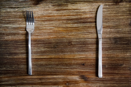 Knife and fork set on a wooden vintage table photo