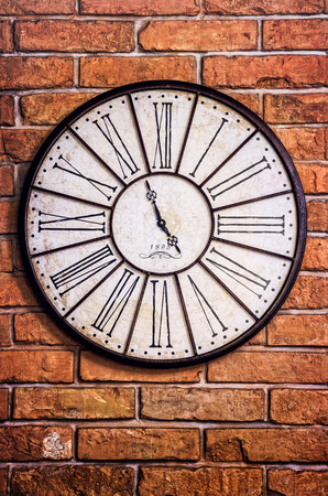 Detail of old vintage clock on textured brick wall photo