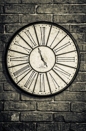 Detail of old vintage clock in monochrome on textured brick wall photo