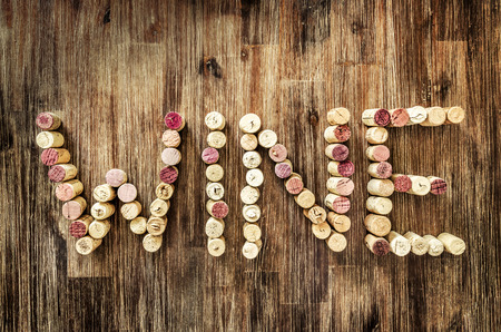 Sign wine made from corks laid on wooden vintage table photo