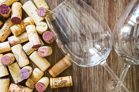 Detail of wine glasses and corks on textured wooden table photo