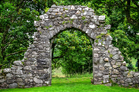 Old stone entrance wall in green landscaped garden