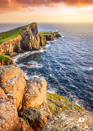 Vertical view of Neist Point lighthouse with rocks in foreground and rocky coastline, Scotland photo