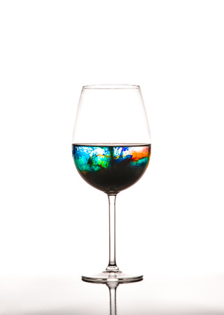 Glass with multicolored water on white background, concept of polution photo