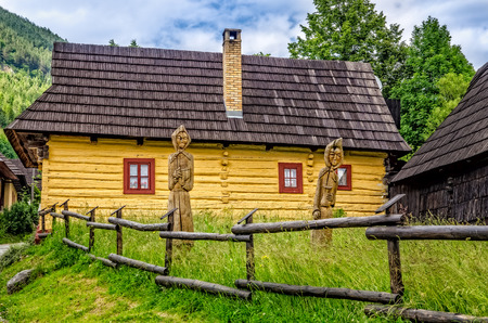 venerable: View of traditional village house and wooded statues, Vlkolinec, Slovakia