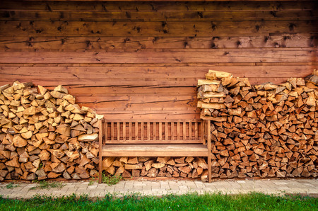 Detail of empty wooden bench with pile of firewood photo