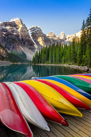 Landscape view of Moraine lake with colorful boats foreground, Canadian Rocky Mountains