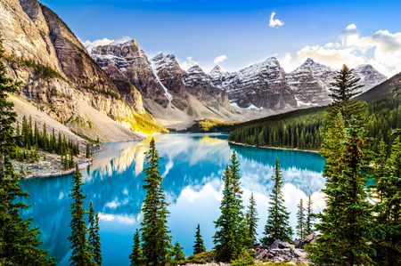 banff national park: Landscape view of Moraine lake and mountain range at sunset in Rocky Mountains, Canada