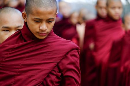 AMARAPURA, MYANMAR - JUNE 28, 2015: Buddhist monks queue for lunch in front of Mahagandayon monastery on 28 June 2015 in Amarapura.