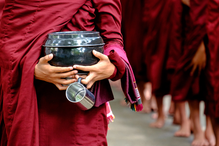 robes: Detail of buddhist monks crowd in red robes and person holding a bowl and cup