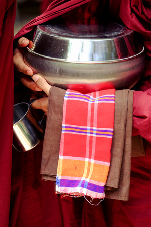 monk robe: Close up of buddhist monk in a robe and his hands holding a bowl and cup
