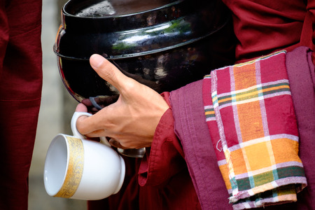 buddhism prayer belief: Detail of buddhist monk in red robe, his hands holding a bowl and cup Stock Photo