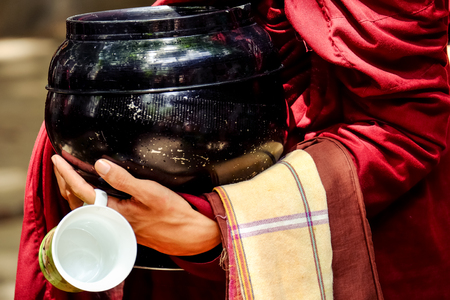 lamaism: Detail of buddhist monk hands holding a bowl and cup