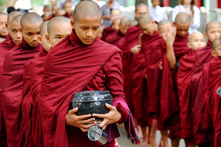 lamaism: MYANMAR, AMARAPURA - JUNE 28, 2015: Buddhist monks queue for lunch in front of Mahagandayon monastery on 28 June 2015 in Amarapura.