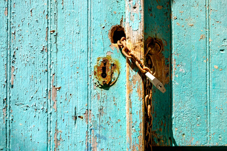 rusty chain: Old rusty padlock and chain on weathered textured door