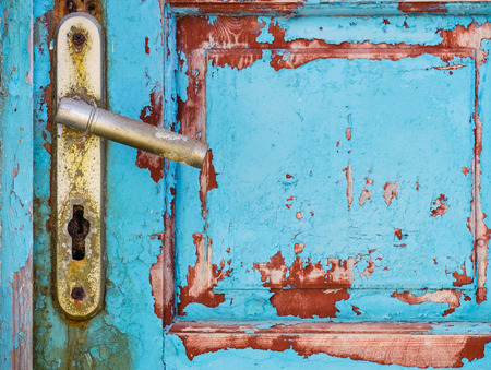 entrance gate: Detail of metal knob on old rusty textured colorful wooden door Stock Photo