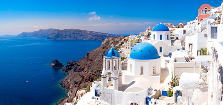 greece: Panoramic scenic view of beautiful white houses and blue domes in Oia, Santorini, Greece