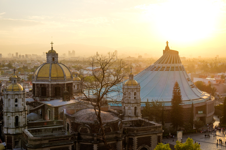 Scenic view of old and new Basilica of Guadalupe with Mexico city skyline at sunset, Mexico