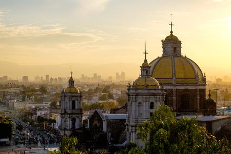 Toneel mening bij Basiliek van Guadalupe met de stad Mexico skyline bij zonsondergang, Mexico Stockfoto