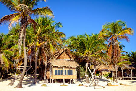 beach landscape: Beautiful summer beach landscape with wooden cabin and palm trees, Tulum, Mexico Stock Photo